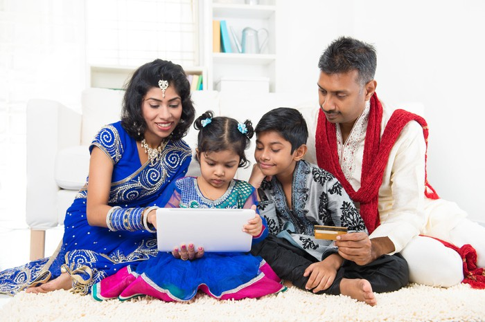 An family gathered around a laptop, with the Dad holding a credit card, making an e-commerce purchase.