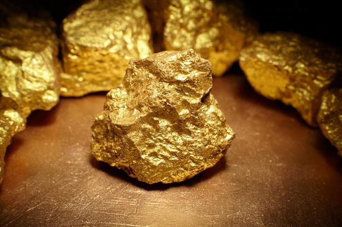 A gold nugget sitting on a surface with gold nuggets lined up behind it in a circle.