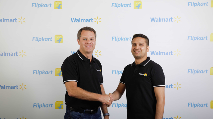 Walmart CEO Doug McMillon shakes hands with Flipkart co-founder Binny Bansal.