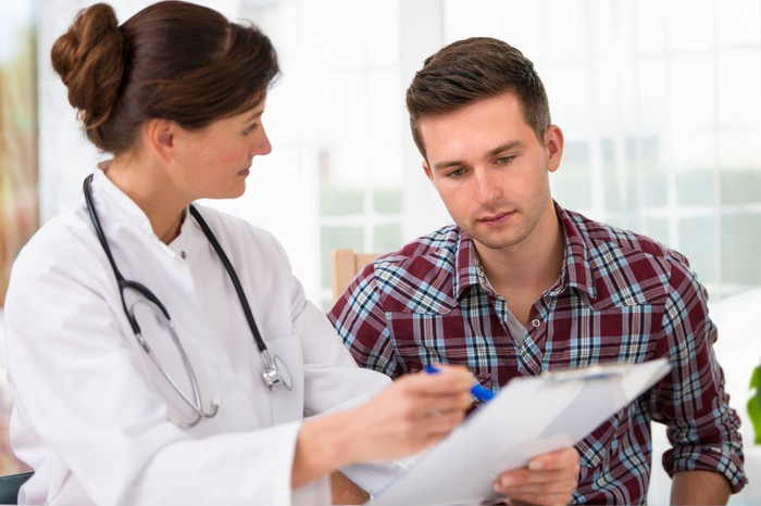 Doctor showing a male patient something on a clipboard