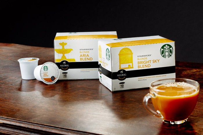 Two boxes of Starbucks K-Cups on a table, along with two K-Cup pods and a cup of coffee