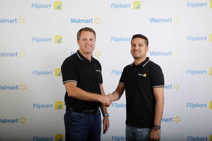 Walmart CEO Doug McMillon and Flipkart co-founder Binny Bansal shaking hands.