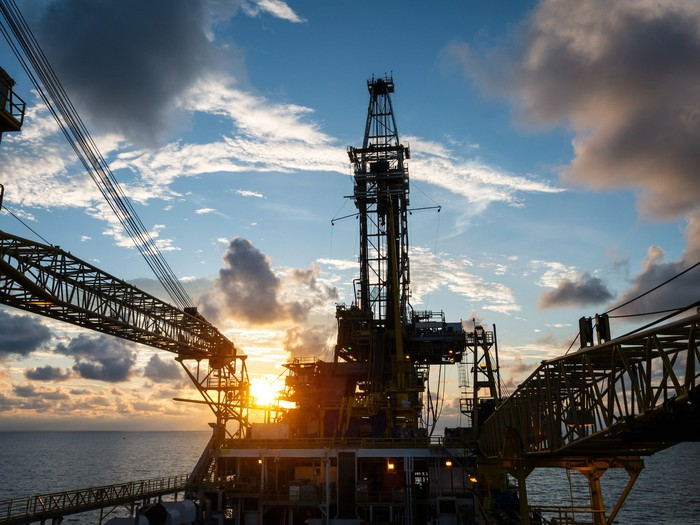 An offshore drilling rig with the sun rising behind it.