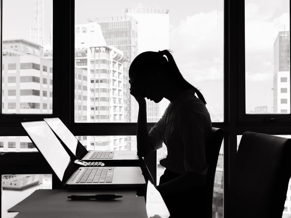 Woman at laptop looking distressed
