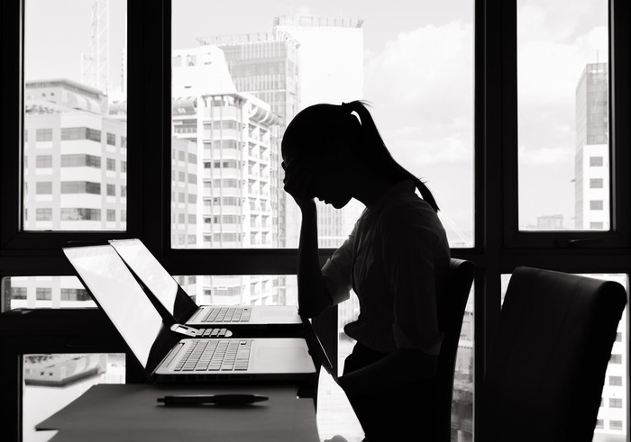 Woman sitting at laptop with her palm pressed to her forehead.