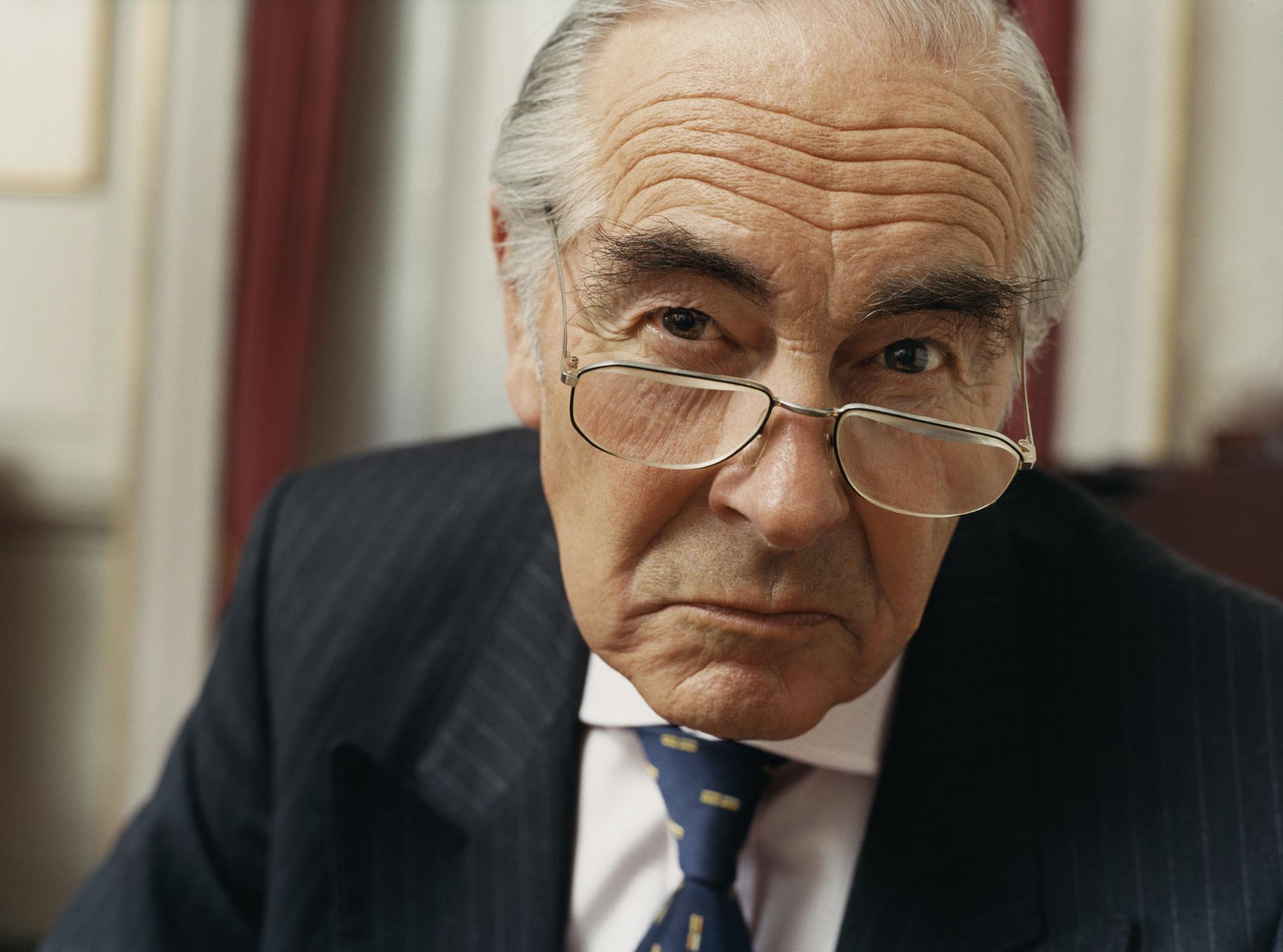 A scowling elderly rich man in a suit.