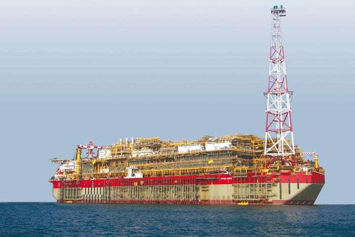 Large drillship vessel at sea with large derrick at one side of the vessel.