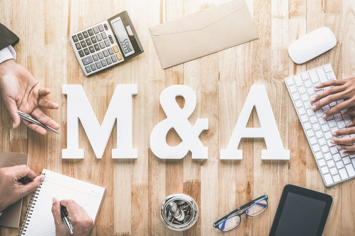 Mergers and acquisitions concept: M and A letters with business items.