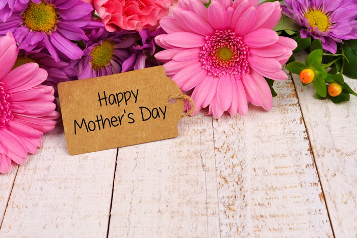 A happy Mother's Day sign sits in front of some flowers.