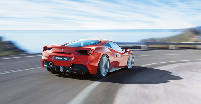 A red Ferrari 488 GTB, a two-seat, mid-engined sports car powered by a V8 engine, is shown at speed on a twisty mountain road.