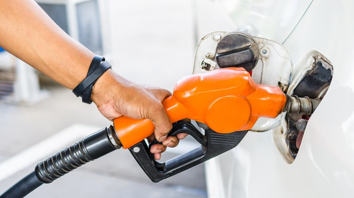 Man holding an orange fuel pump as he puts gas in his vehicle