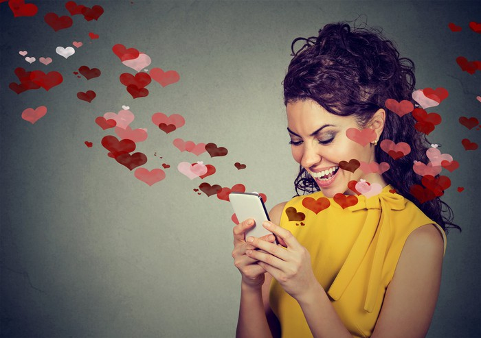 Woman smiling at her phone screen as animated hearts fly out of it