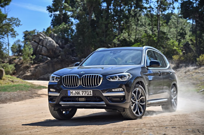 A dark blue 2018 BMW X3, a compact luxury crossover SUV, on a dirt road