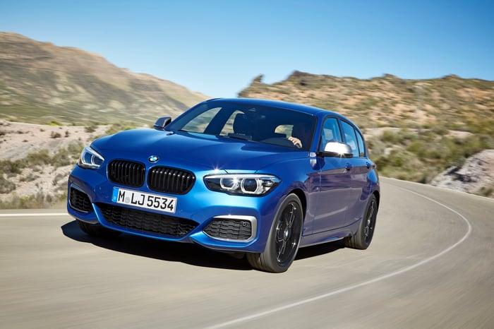 A blue BMW 1 Series, a small premium sedan, on a mountain road