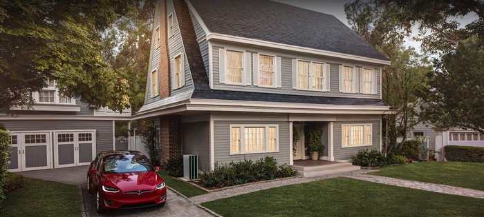 A gray house with a red Tesla Model 3 parked next to it in the driveway.