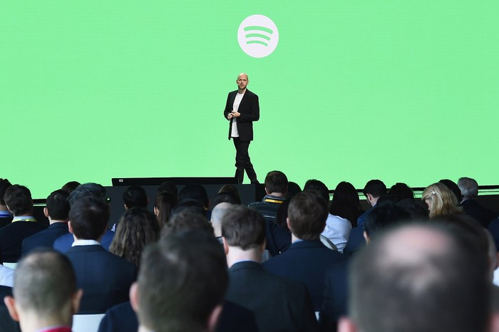Person on stage with large audience in front of a green screen with Spotify's logo on it.