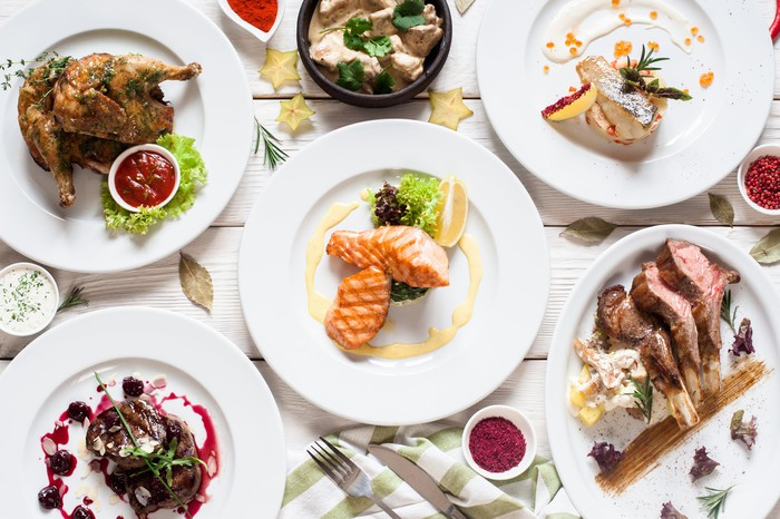 Various food dishes on white plates.