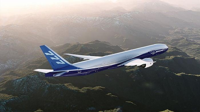 A Boeing 777-300ER flying over mountainous terrain
