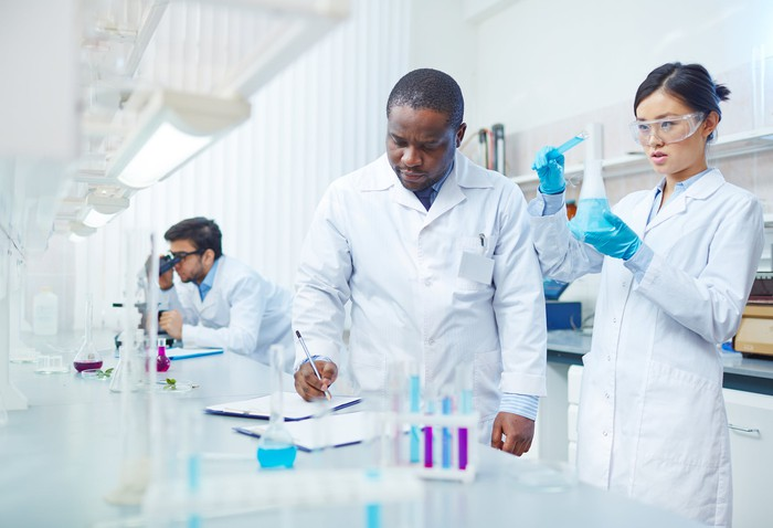 Three scientists in lab with one in background looking through microscope, one writing on notepad, and another holding a beaker.