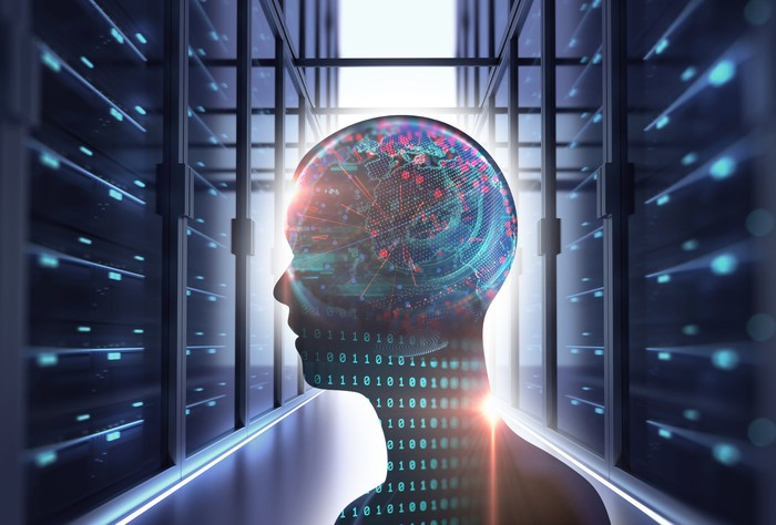 The inside of a data center with the outline of a person's head, filled with 0s and 1s and other things in the digital realm, in the foreground -- concept for AI.