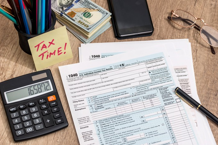 A desktop with a calculator, some pencils, a stack of $100 bills, a pair of glasses, a checkbook, and a note that says tax time next to some tax forms.