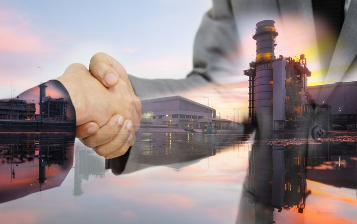 Two people shaking hands with an industrial site in the background.