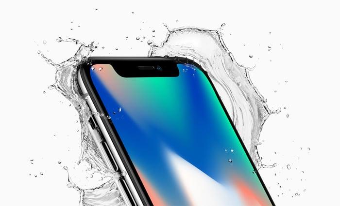 Close-up shot of an Apple iPhone X splashing through some water.