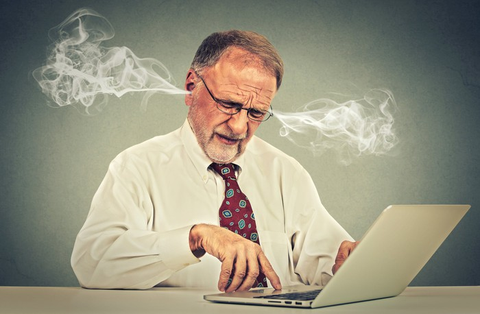 Steam is coming out of the ears of a man in a shirt and tie as he looks at his computer screen.