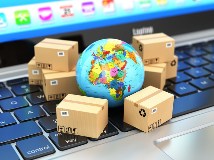 A miniature globe on top of a computer keyboard with shipping boxes stacked around it.