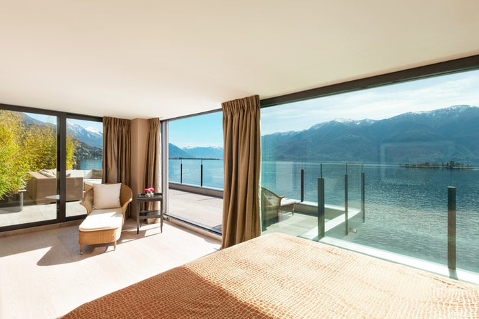 Hotel suite overlooking clear mountain lake.
