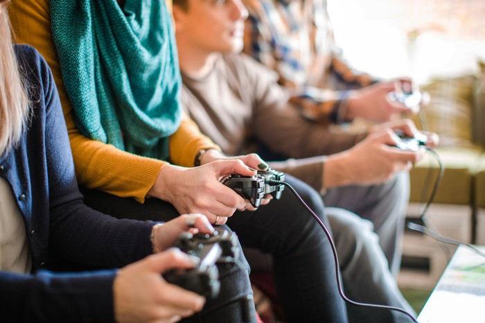 Teens holding controllers and playing video games.