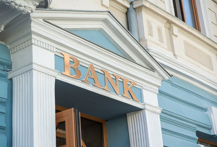 "The exterior of a building with the word ""BANK"" written on it."