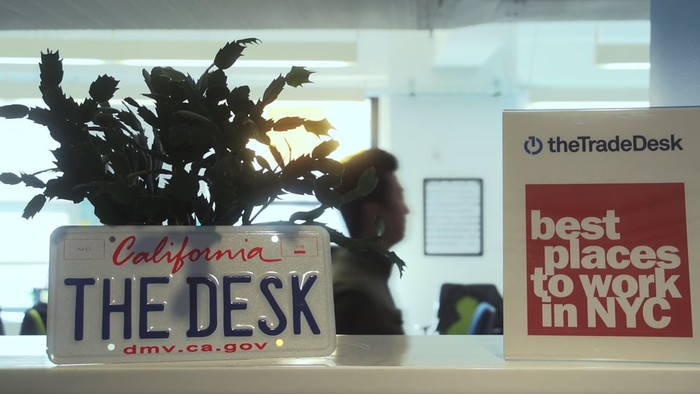 A California license plate with the words THE DESK on a front desk, along with a sign that says the Trade Desk best places to work in NYC.