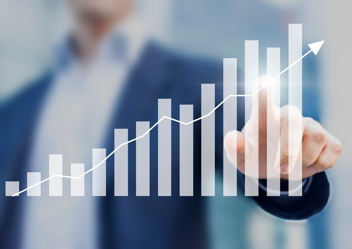 Man in suit touching line/bar chart indicating gains