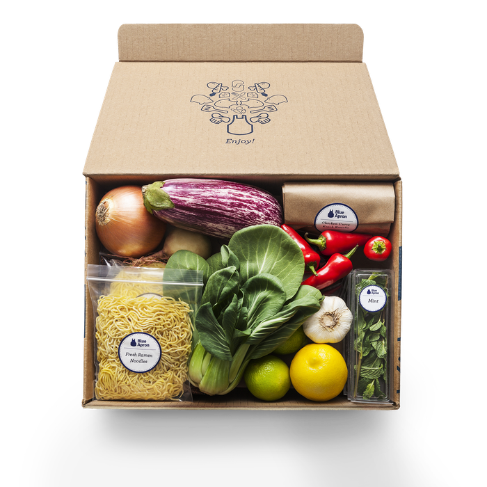 A Blue Apron box with various fresh ingredients like lettuce, red peppers, and onions