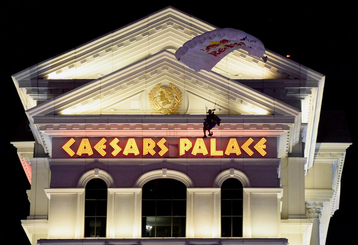 Person falling with a parachute in front of Caesars Palace location at night.