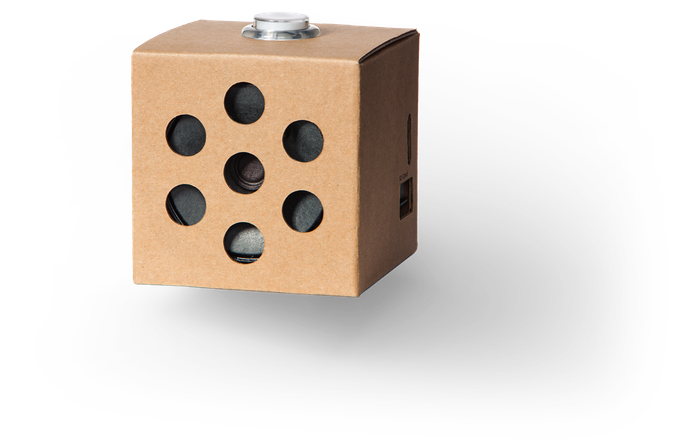 A small cardboard box with holes on the front that houses the Google Voice AIY kit.