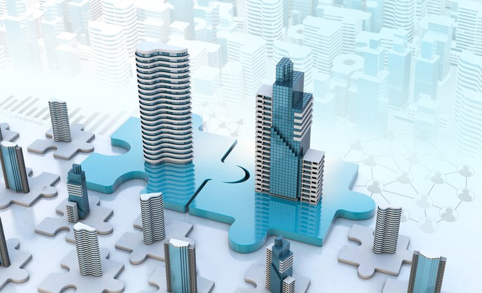 Two buildings on puzzle pieces, symbolizing a merger.