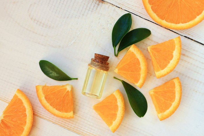 Slices of oranges scattered on a table with a small vial of citrus oil laying in the middle.