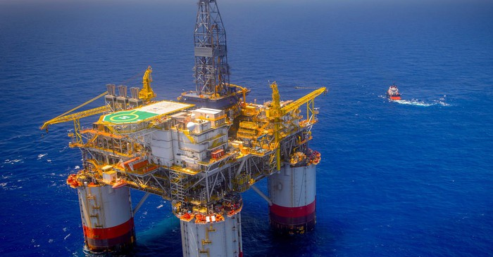Offshore drilling rig at sea with small boat in background.