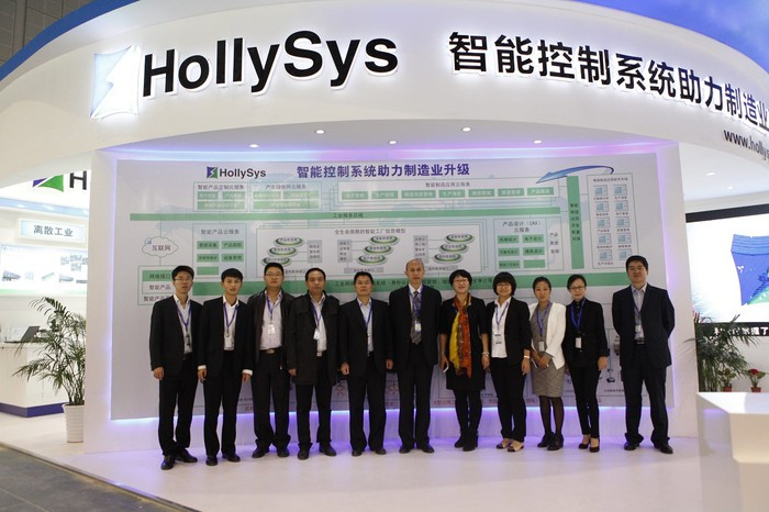 11 people standing under an awning with the Hollysys logo at a conference.