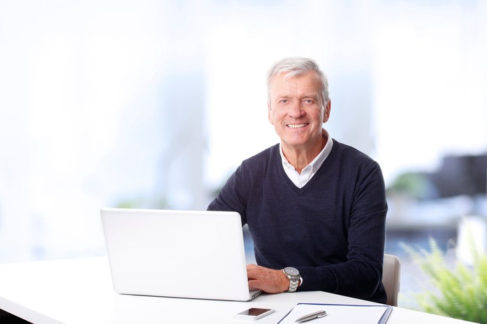 Older man sitting at a laptop, smiling