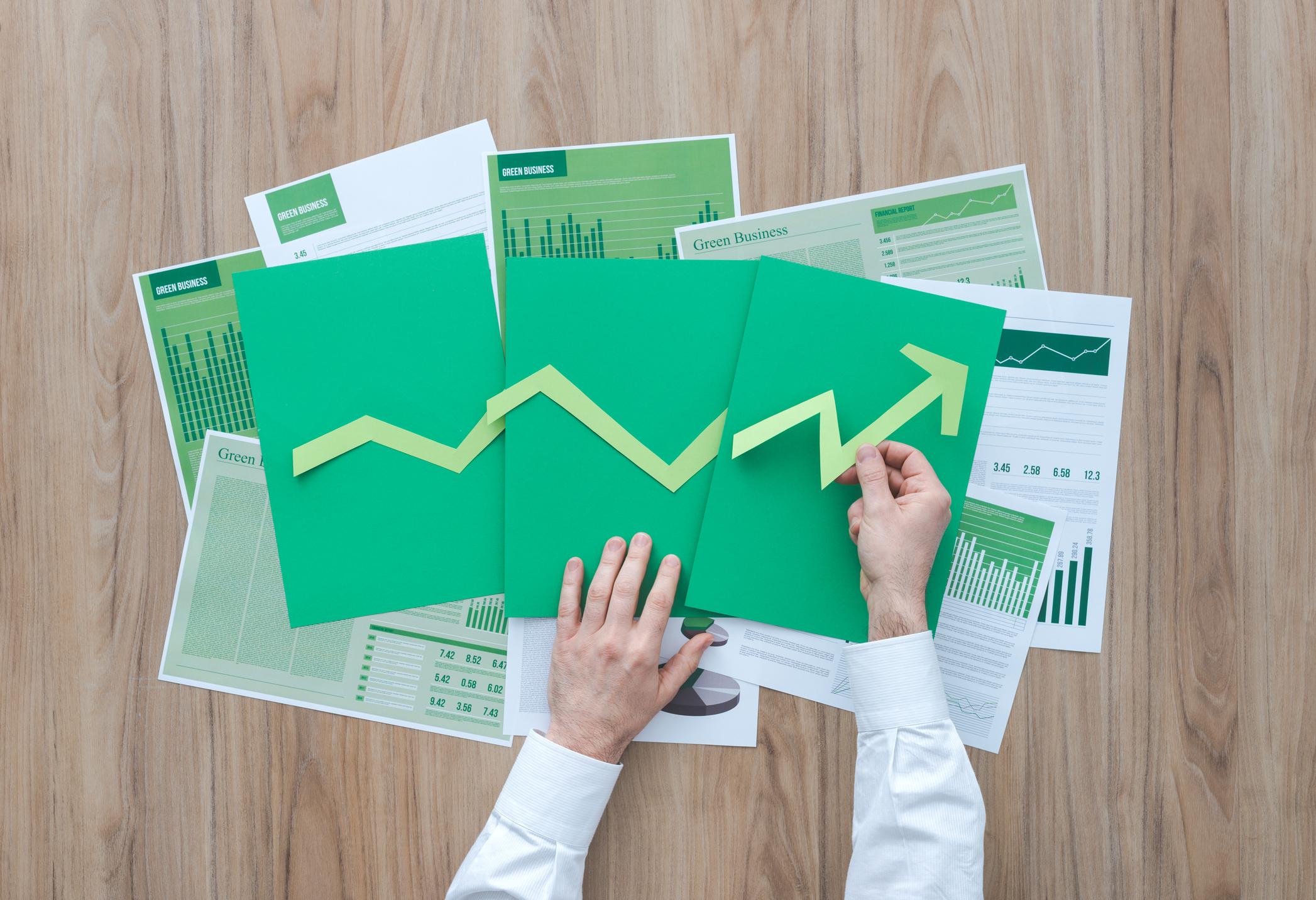 A person's hands arrange cut out construction paper into an upward trending arrow.