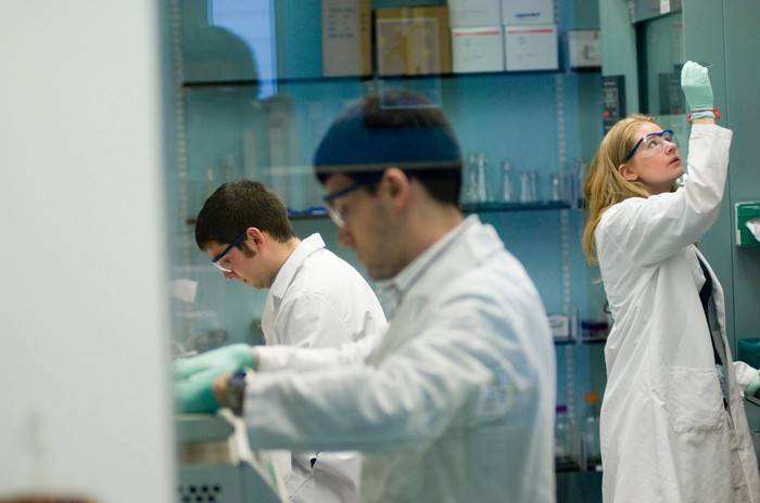 Scientists in white labcoats working in a lab.