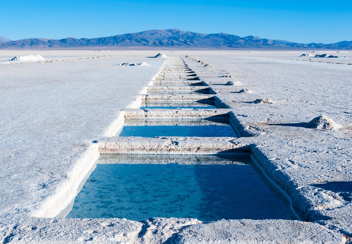 A salt flat showing lithium evaporation ponds with a mountain and blue sky in background.