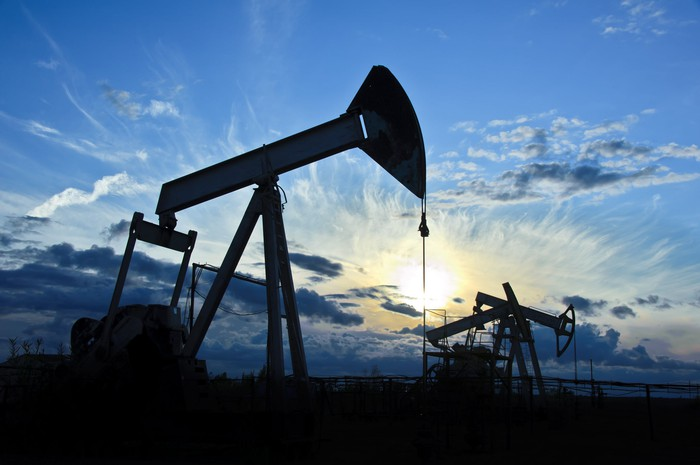 Oil pumps with a blue sky and the sun behind them.