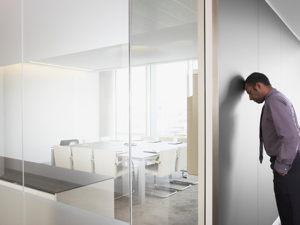 Man with head against wall in conference room