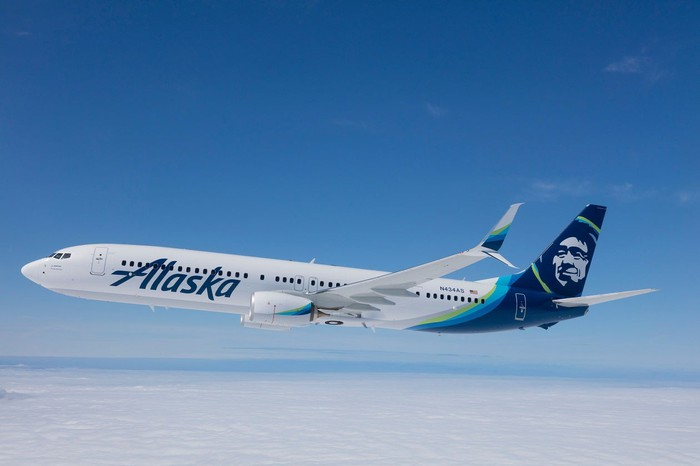 Jet aircraft bearing Alaska brand and logo in flight on a clear day.
