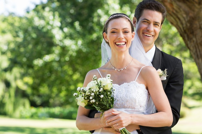 Groom putting his arms around bride with bouquet in hands