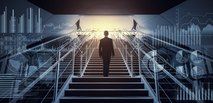 Man climbing stairs surrounded by stock graphs.